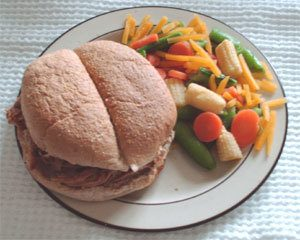 pulled pork sandwich served with side order of steamed veggies
