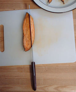 cooked yam slice being cut