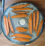 sweet potatoes cut into strips placed in a dehydrator to make treats for dogs
