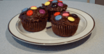 3 chocolate cupcakes iced and decorated with Smarties used as a header image