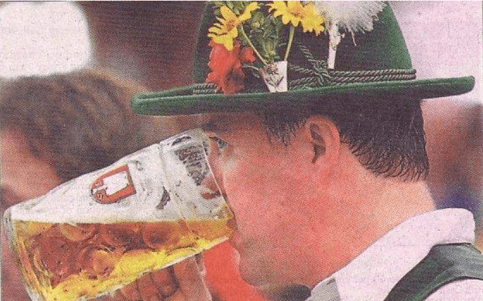 picture of a newspaper picture of a man drinking what looks like a pint of beer in a glass mug