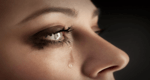 close up of a side-view of woman's face with a tear coming out of her eye, used as a header image