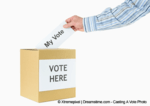 photograph of a person's hand, placing their vote into a ballet box, used as a header image