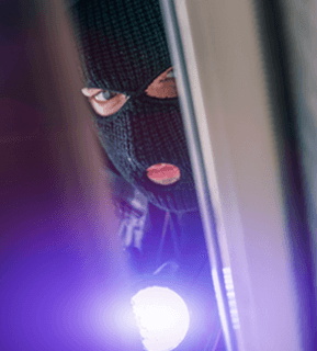 masked human peering in with flash light