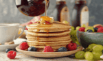 image of a stack of pancakes with someone pouring maple syrup over them
