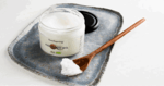 jar of coconut oil along with a wooden spoon full of it, both sitting on a tray