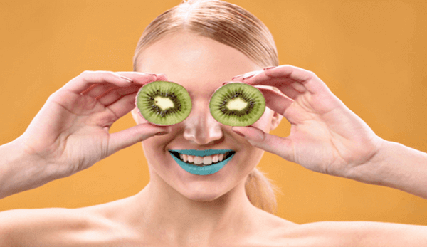 a head and shoulder picture of a blonde lady holding pieces of kiwi fruit slices in front of her eyes and wearing blue lipstick