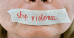 "close up of a human's mouth with masking tape over top. The making tape has ""stop violence"" written on it."