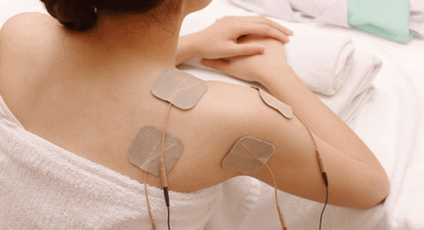 ladies shoulder showing her using 4 small massage pads