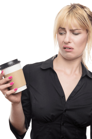 lady holding a takeout cup and looking at it with her lip in the air like she is not pleased with the drink