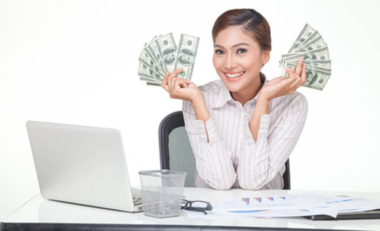 lady holding cash in her hands while sitting at her desk, in front of her laptop computer